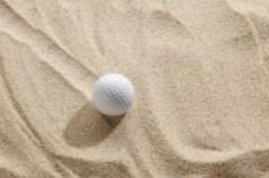 バンカーに入ってしまったゴルフボールの画像